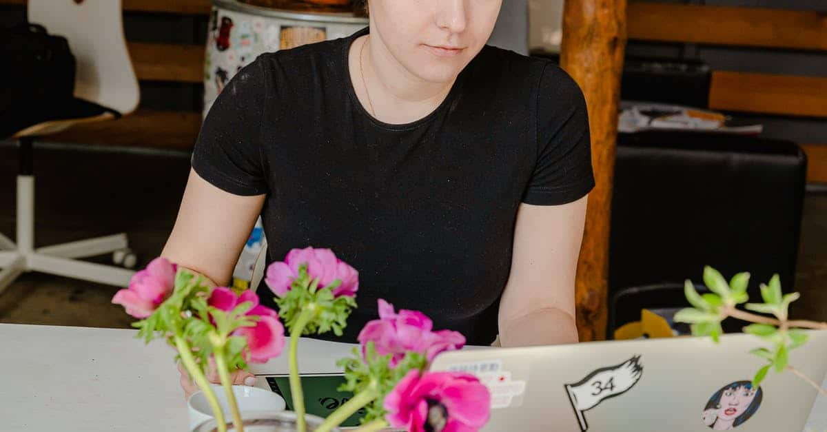 A young boy sitting at a table with a vase of flowers