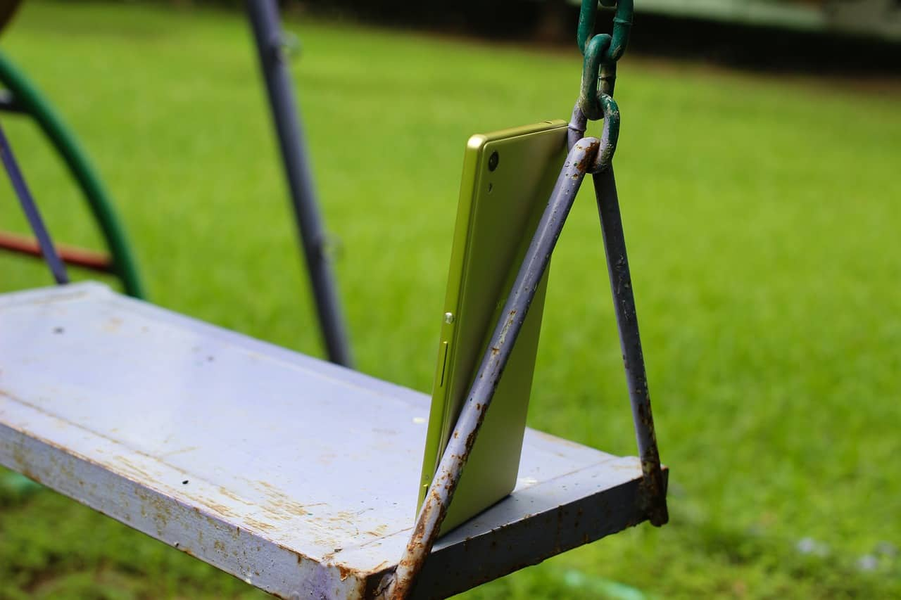 A close up of a green park bench sitting in the grass