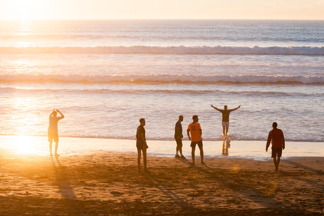 A group of people standing on top of a sandy beach